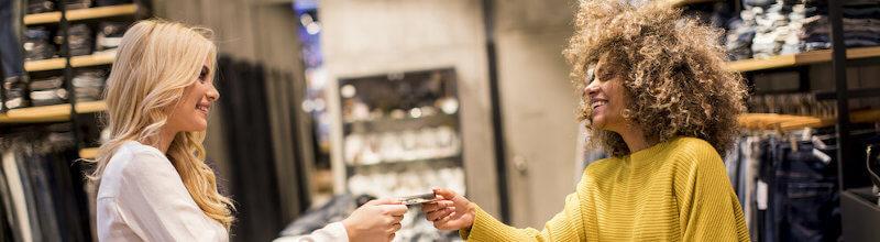 Glücklicher Fraukunde, der mit Kreditkarte im Modeschauzimmer zahlt