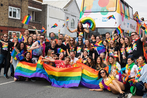The Qualtrics team, posed as a group in front of the Qualtrics + SAP double decker Pride bus, at the 2019 Dublin Pride parade