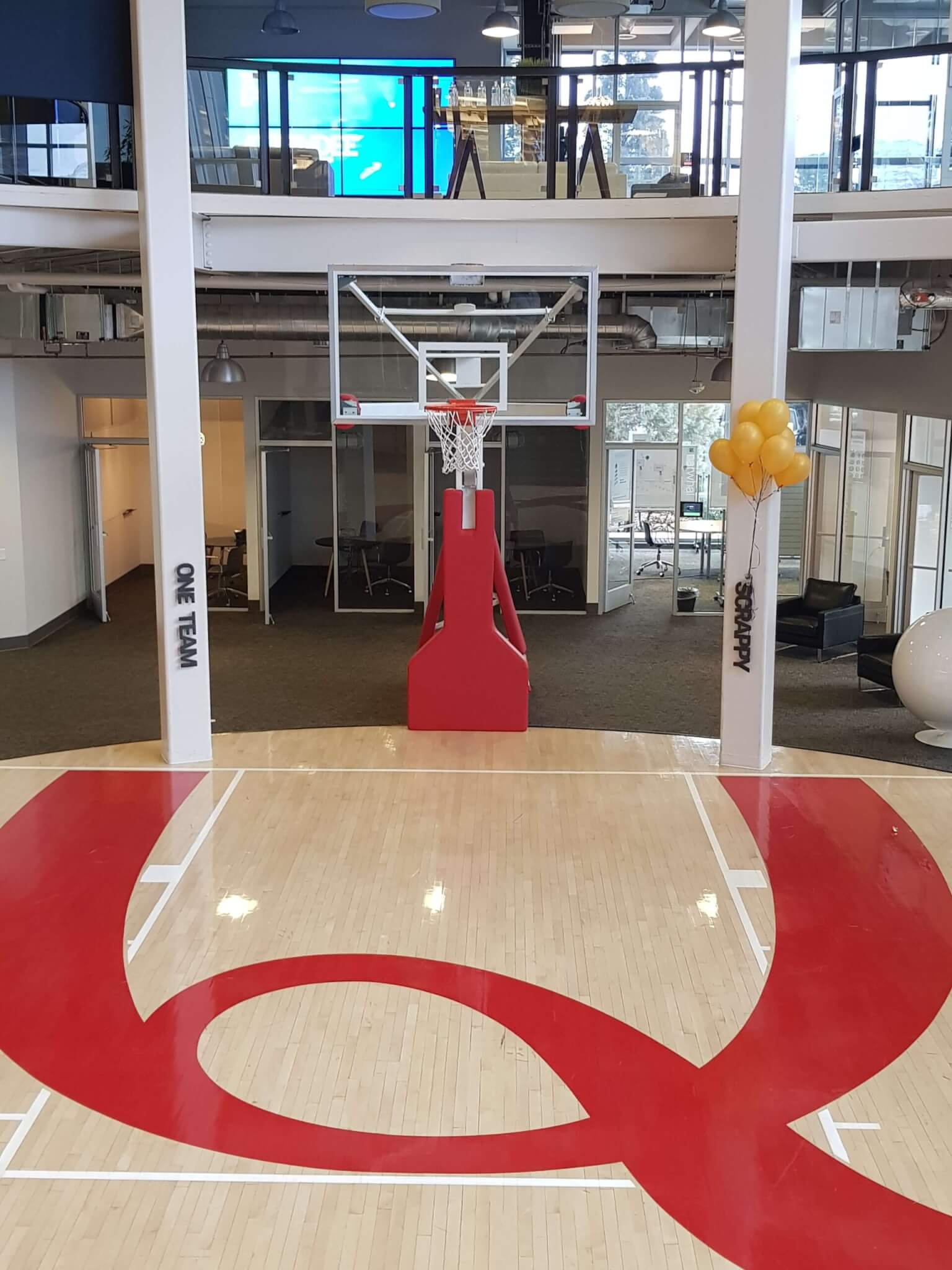 The Qualtrics Provo HQ main entry, which features a basketball court with a giant red letter Q on the floor. PIctured also is 2 of the 5 TACOS pillars - One Team & Scrappy