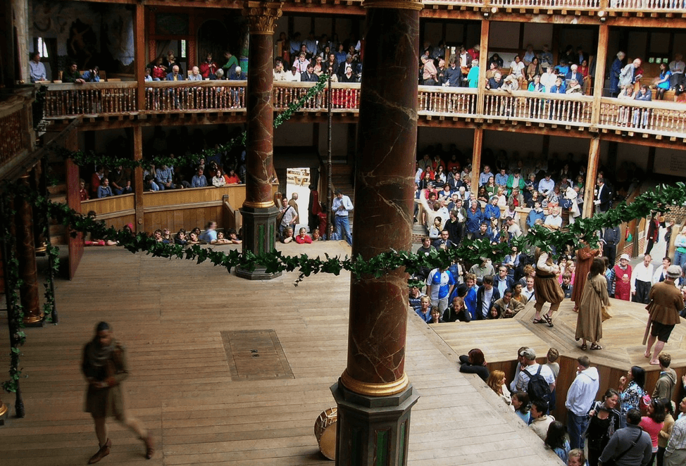 An actor performs on the stage of the globe for a large crowd